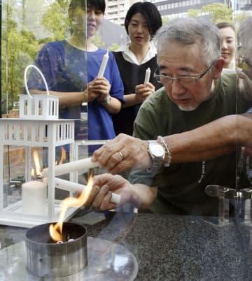 「1.17希望の灯り」の火を台湾に運ぶため「分灯」する垂水英司さん(手前)=17日午後、神戸市