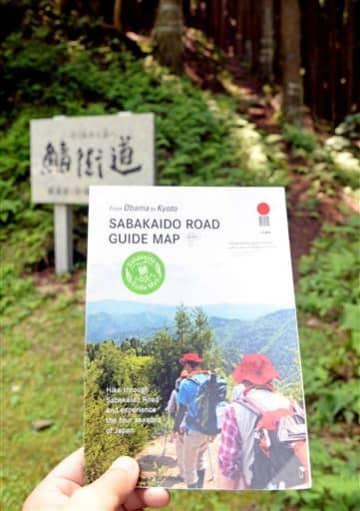 福井県小浜市が作った英語版の鯖街道マップ。奥に見えるのは紹介されている針畑越えの山道=同市上根来