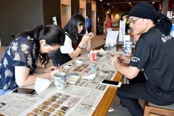 宿泊客に絵付けを指南する鶴丸修さん(右)=唐津市のホテル&リゾーツ佐賀唐津