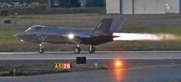 基地内に照明がともる中、夜間の飛行訓練に向け滑走路を離陸するF35A=17日午後5時54分