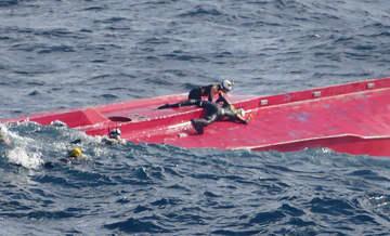 転覆した「第65慶栄丸」の船体の調査をする潜水士=18日午後、根室市の納沙布岬東方沖(第1管区海上保安本部提供)