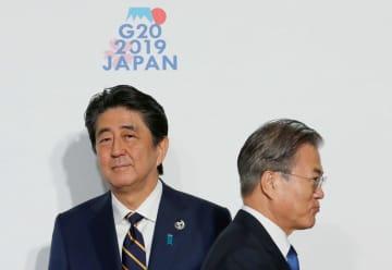 6月、G20大阪サミットで握手した後、すれ違う韓国の文在寅大統領(右)と安倍首相