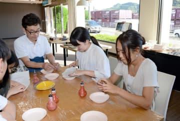 イッチン技法による装飾を体験する学生たち=有田町外尾町の佐賀県陶磁器工業協同組合