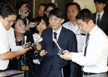 日韓局長協議を終え、報道陣に囲まれて外務省を出る韓国外務省の金丁漢アジア太平洋局長(中央)=20日午前