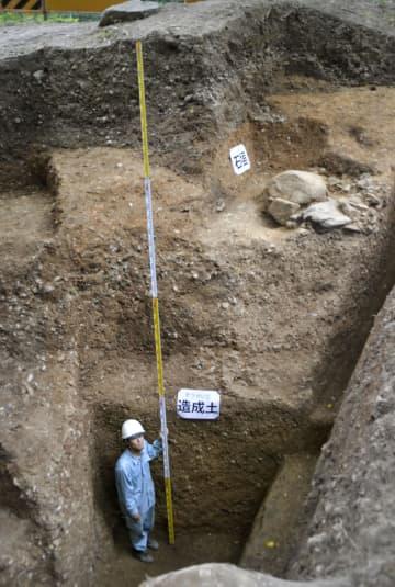 発掘調査で見つかった深さ3.3メートル以上の造成土。右上は武家屋敷とみられる石垣の一部=20日午後、京都市伏見区