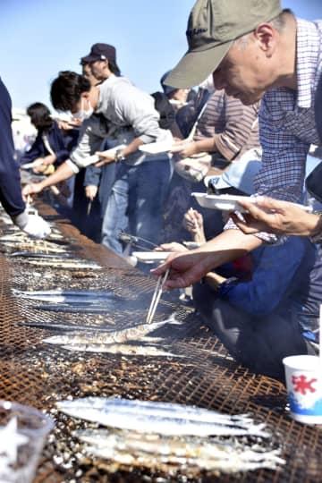 「根室さんま祭り」でサンマを焼く参加者=21日午後、北海道根室市