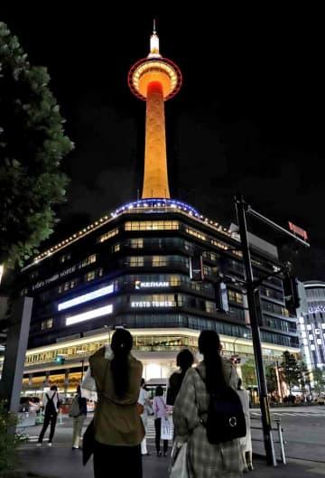 「世界アルツハイマーデー」に合わせ、オレンジ色にライトアップされた京都タワー(21日午後7時9分、京都市下京区)