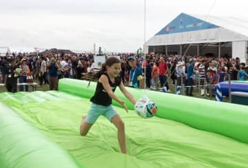 ラグビー体験で落ちてくるボールをキャッチする女児=横浜市西区の臨港パーク