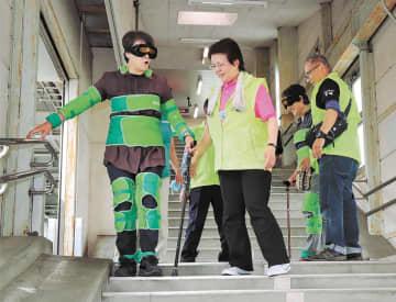 体に重りを着けて階段を歩き、高齢者や妊婦の苦労を疑似体験した6月のイベント