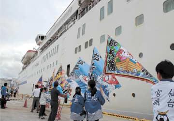 接岸する大型客船を地元観光関係者が大漁旗を振って出迎えた