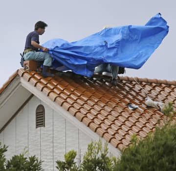 温帯低気圧となった台風17号の影響で強い風が吹く中、先の台風で被害を受けた住宅の屋根にブルーシートを張る人たち=23日午後、千葉県鋸南町