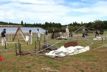 強風で倒れたテントを撤去するイベント関係者=23日、阿賀野市村杉の「五頭山麓うららの森」