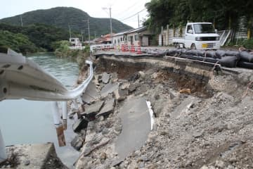佐須川が増水して崩落した県道桟原小茂田線=23日午後4時35分、対馬市厳原町下原