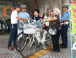 自転車の利用者に施錠を呼び掛ける加古川署員=加古川市加古川町篠原町