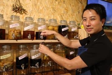 果実酒をカップに注ぐ渕上さん=長崎市鍛冶屋町、農家バー「NaYa」