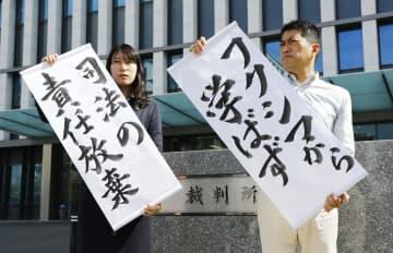 九州電力玄海原発3、4号機の運転差し止めを求めた仮処分の即時抗告審で、福岡高裁が差し止めを認めず「司法の責任放棄」などの垂れ幕を掲げる弁護士=25日午後、福岡高裁前