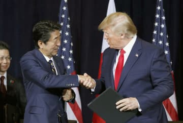 日米貿易協定締結で最終合意し、共同声明への署名を終えて握手する安倍首相(左)とトランプ大統領=25日、米ニューヨーク(共同)