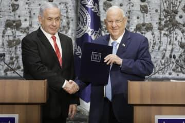 25日、イスラエルのエルサレムで握手するネタニヤフ首相(左)とリブリン大統領(AP=共同)