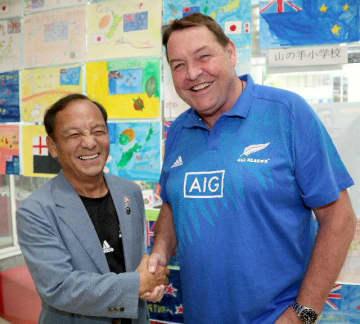 NZ代表のスティーブ・ハンセン監督(右)との再会を喜び、握手を交わす西謙二さん=26日、別府市のトキハ別府店