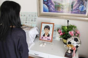 亡くなった息子の遺影を見つめる母親。サッカーが好きな少年だった=9月、熊谷市の自宅