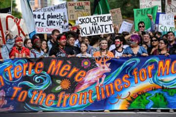 27日、カナダ東部モントリオールで抗議デモに参加したグレタ・トゥンベリさん(中央)ら(ロイター=共同)