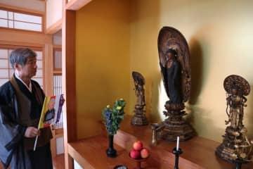 教伝寺で公開される阿弥陀如来像を前に公開寺院の目印の旗を持つ小泉住職(南丹市園部町新町・同寺)
