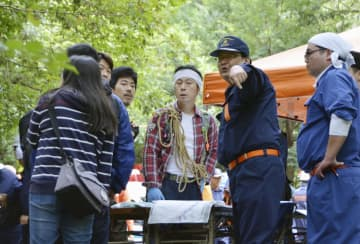 行方不明となっている小倉美咲さんの捜索に加わり、消防団員(右から2人目)と打ち合わせるボランティア=29日、山梨県道志村