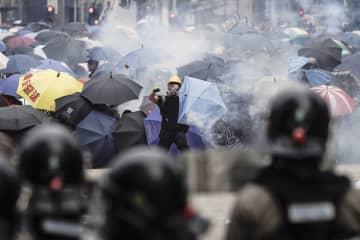 警官隊(手前)が放った催涙弾を投げ返す男性(中央)。後方は傘を差して身を守るデモ隊=29日、香港(共同)