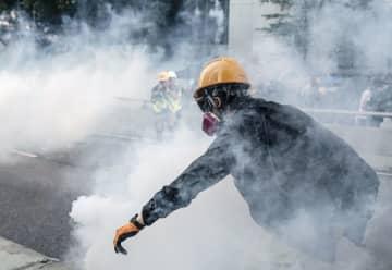香港で警官隊が撃った催涙弾から逃げるデモ隊=1日(共同)