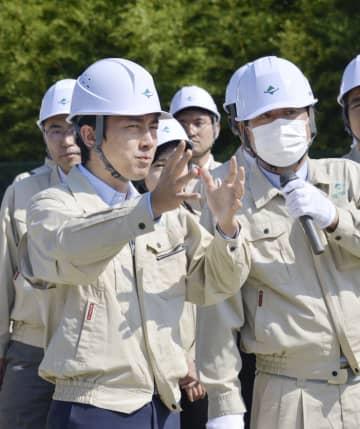 汚染土の仮置き場を視察する小泉環境相(左)=2日、福島県楢葉町