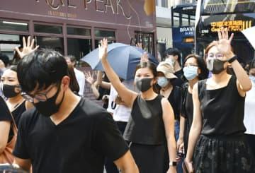 2日、香港中心部で5本の指を広げ「五大要求」の実現を訴えるデモ隊(共同)