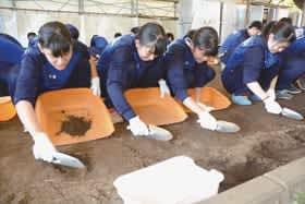 土を掘り進め遺跡発掘を体験する伊達緑丘高校の生徒