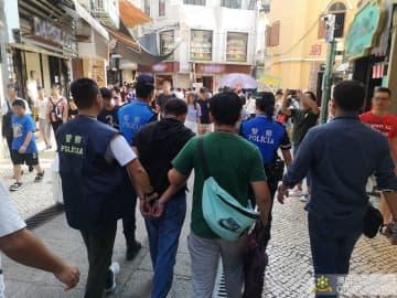 防犯パトロール中の警察官がスリの現行犯で逮捕した男を連行する様子(写真:マカオ治安警察局)