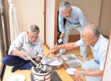 「おへら焼き」に臨み、へらの上で丸い餅を焼く当人様の藤原さん(右)と烏帽子親の熊谷さん(左)
