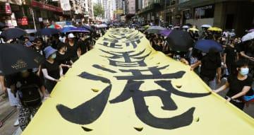 香港で「覆面禁止法」の施行などに抗議し、スローガンを掲げて歩く人たち=5日(共同)
