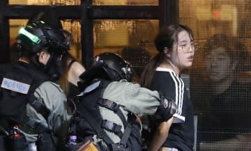 大規模デモが行われた香港中心部で、警察に拘束される若者。奥のカフェから男性が見つめていた=6日(共同)
