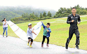 ビニールの袋で空気を集めながら走る子どもたちと一緒に走る室屋選手(右)