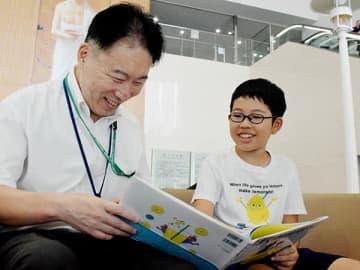 絵本を受け取った武久秀夫さん(左)と談笑する栄島四郎君=日高市の埼玉医科大国際医療センター