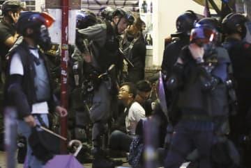 無許可のデモが行われた香港中心部で警察に拘束された男性(奥中央)ら=6日、香港(共同)
