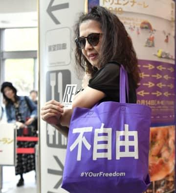 国際芸術祭「あいちトリエンナーレ2019」のチケット売り場近くで、「不自由」と書かれたバッグを肩に掛ける女性=8日午前、名古屋市東区の愛知芸術文化センター