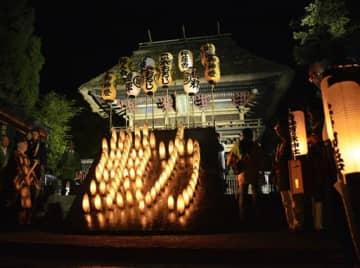 青井阿蘇神社前の楼門前に竹灯籠でともされた「動」の火文字=人吉市