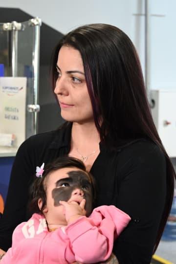 ロシア南部クラスノダールに到着し、娘のルナちゃんを抱く米国人キャロル・フェンナーさん=9月25日(タス=共同)
