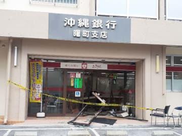 乗用車が突っ込み入り口のドアやカウンターが壊れた銀行=9日午後1時ごろ、那覇市曙