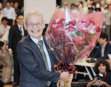 時事通信 記者会見で花束を手に笑顔を見せる吉野彰氏