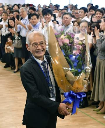 ノーベル化学賞の受賞決定から一夜明け、旭化成本社で花束を手にする吉野彰名誉フェロー(左)=10日午前、東京都千代田区