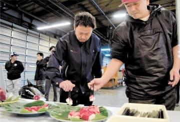 メバチマグロのにぎりずしを試食する市場関係者=10日午前6時20分ごろ、仙台市若林区の市中央卸売市場