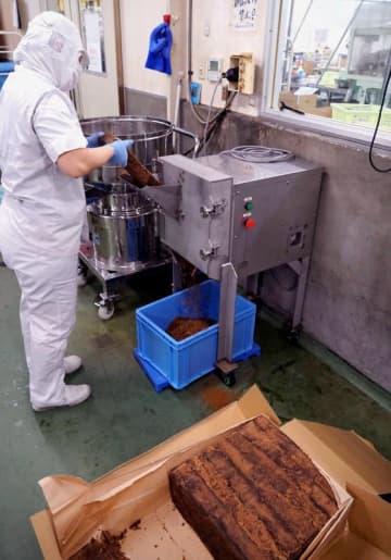 祥メタル製作所が開発した黒糖荒削り機を使い、加工用として黒糖をフレーク状に削る従業員=9日、黒糖本舗垣乃花のうるま工場