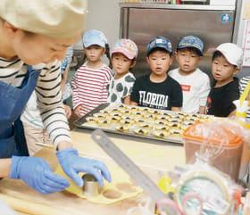 菓子ができる工程を見つめる園児たち