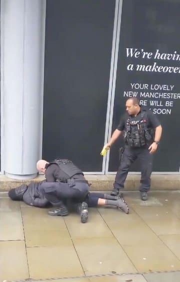 11日、英中部マンチェスターのショッピングセンター付近で、男を取り押さえる警察官(JOHN GREENHALGH氏提供、ロイター=共同)