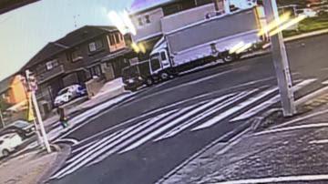 現場付近の防犯カメラ映像。ワゴン車と衝突してトラックを乗り捨て、白の乗用車方向へ歩く容疑者とみられる人物